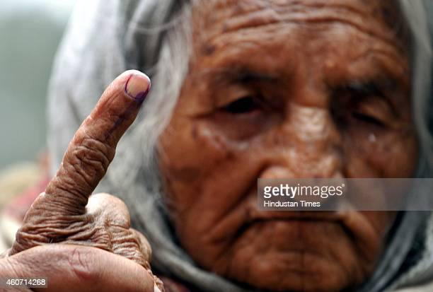 A 100 year old lady showing her ink marked finger after cast her vote at polling station during assembly elections on December 20 2014 in Jammu India...