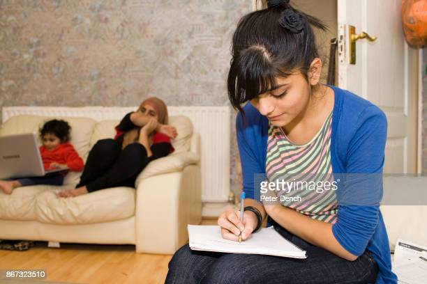 15 year old Laiba Abbasi studying for her exams in the living room of the home where she lives with her mother Safia father Khalid and sisters Maira...