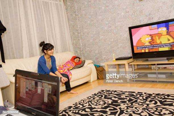 Year old Laiba Abbasi watching an episode of TV favourite, The Simpsons, with her sister Fatimah . Her sister Ahareem is playing card game patience...