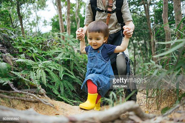 1 year old little girl walking in nature with mother
