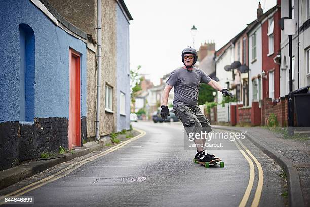 50 year old long boarder riding along a street