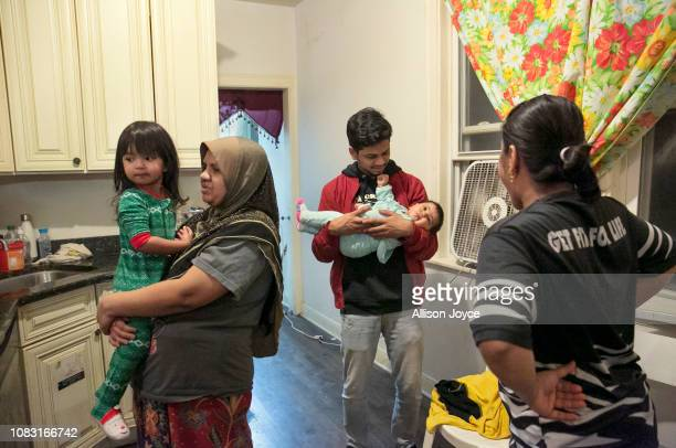 25 year old Maimunah Shukor holds her daughter 3 year old Norfarzana while her siblings chat in the kitchen on January 12 2019 in Chicago Illinois...