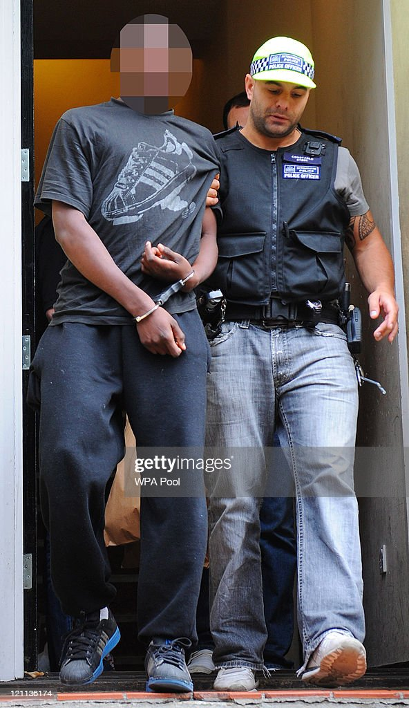 A 17 year old male suspect is arrested at a property on Villa Road, Brixton for violent disorder in connection with recent rioting and looting in the capital on August 14, 2011 in south London, England. As part of 'Operation Withern', Metropolitan police officers carried out a series of raids before 0730hrs on eight addresses in south London and recovered evidence for six suspects in connection with the recent outbreaks of rioting and looting throughout London.