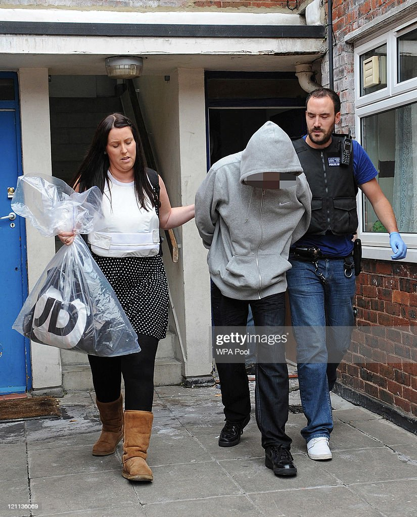 A 15 year old male suspect is arrested for violent disorder and handling of stolen goods in connection with recent rioting and looting in the capital during an early morning raid at an address in Brixton on August 14, 2011 in south London, England. As part of 'Operation Withern', Metropolitan police officers carried out a series of raids before 0730hrs on eight addresses in south London and recovered evidence for six suspects in connection with the recent outbreaks of rioting and looting throughout London.