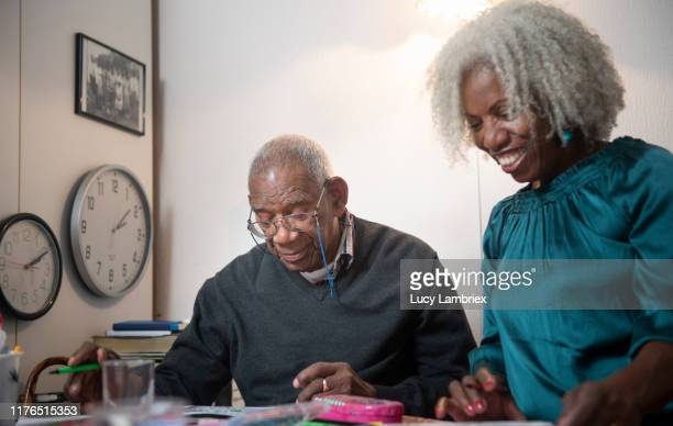 91 year old man colouring at home with his 62 year old daughter - 63 year old female stock pictures, royalty-free photos & images