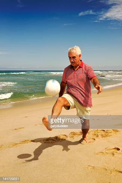 65 year old man playing with ball on a beach