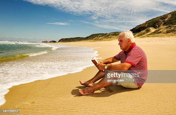 65 year old man reading on a beach