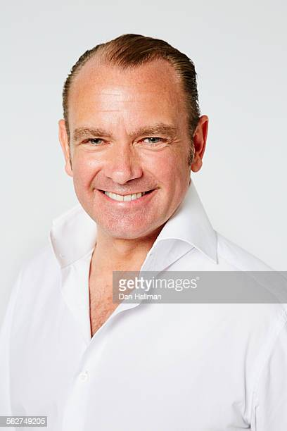 49 year old man smiling at camera on white.