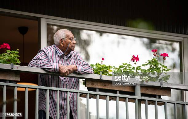 91 year old man standing on his balcony, looking away - 90 plus years stock pictures, royalty-free photos & images