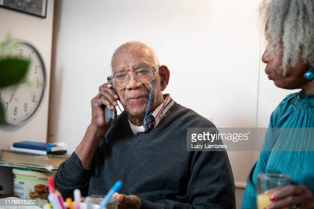 91 year old man talking on the phone, while his daughter is listening - 63 year old female stock pictures, royalty-free photos & images