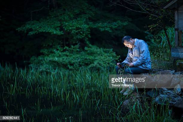 A 60 year old man uses a tablet in the forest