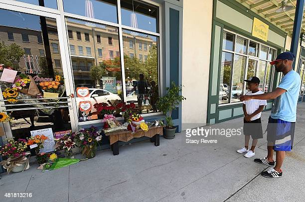 Year old Mason Matthews and his father visit a makeshift memorial outside of a store owned by one of the victims, Jillian Johnson on July 24, 2015 in...