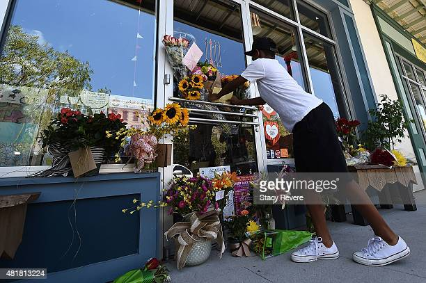 Year old Mason Matthews leaves a card at a makeshift memorial outside of a store owned by one of the victims, Jillian Johnson on July 24, 2015 in...