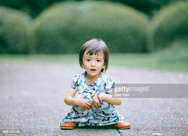 2 year old mixed race girl sitting on road and looking at camera