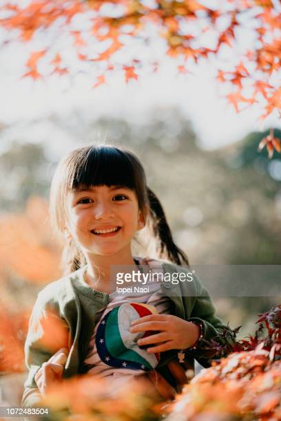 4 year old mixed race girl smiling with red leaves of Japanese maple trees