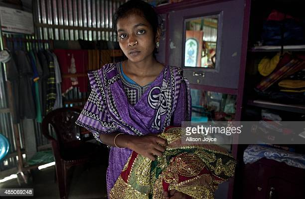 14 year old Mousammat Akhi Akhter poses for a photograph with her wedding sari in her home August 19 2015 in Manikganj Bangladesh Last year when she...