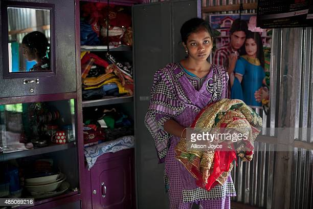 14 year old Mousammat Akhi Akhter stands for a photograph with her wedding sari in her home August 19 2015 in Manikganj Bangladesh Last year when she...