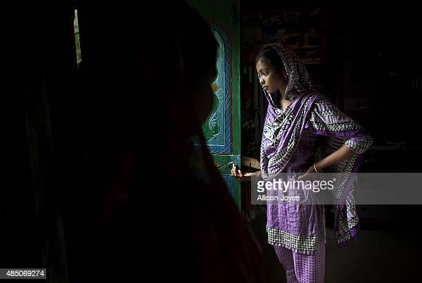 14 year old Mousammat Akhi Akhter stands in the doorway of her home August 19 2015 in Manikganj Bangladesh Last year when she was only 13 Akhi got...