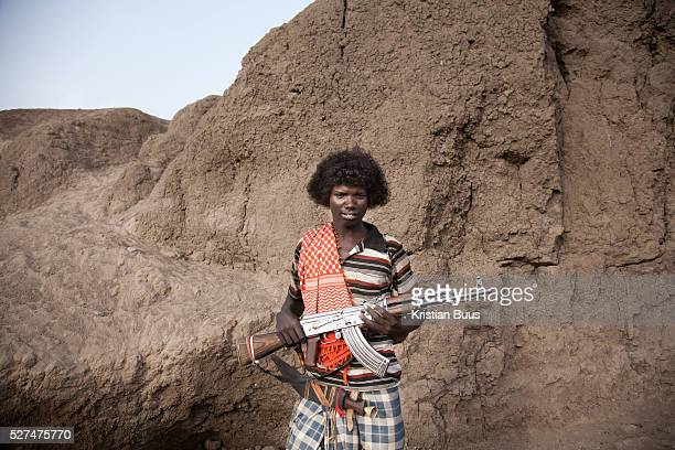 16 year old Muhammed with his trusted AK47 The gun is to protect his livestock from wild animals and rustlers from other local clans The Afars speak...