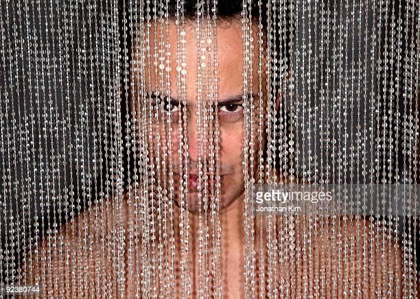 44 year old naked man behind a beaded wall.