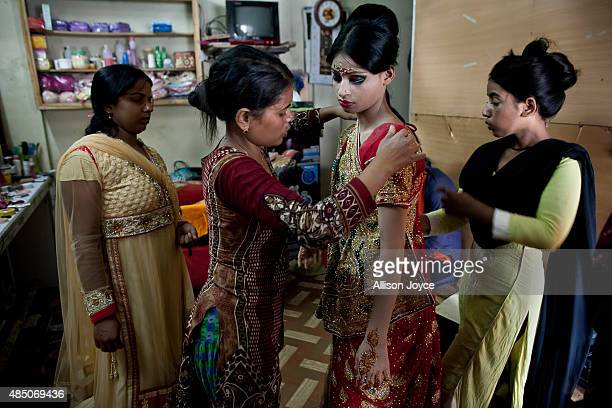 15 year old Nasoin Akhter has her wedding sari wrapped at a beauty parlour on the day of her wedding to a 32 year old man August 20 2015 in Manikganj...
