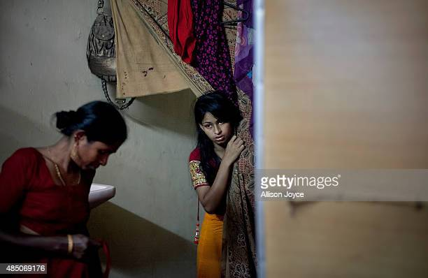 15 year old Nasoin Akhter looks out of a dressing room at a beauty parlour on the day of her wedding to a 32 year old man August 20 2015 in Manikganj...