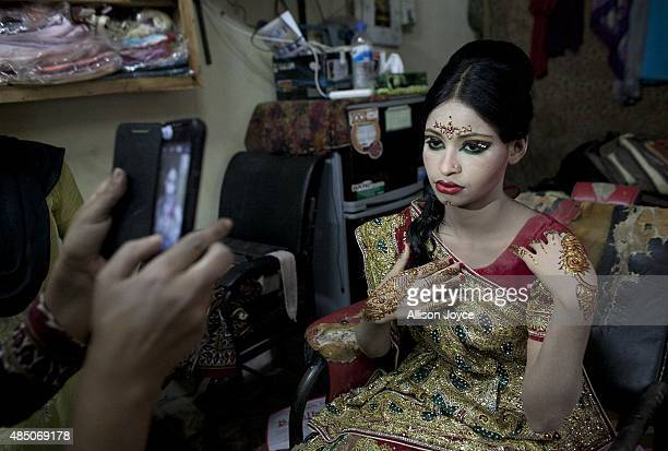 15 year old Nasoin Akhter poses for a photo at a beauty parlour on the day of her wedding to a 32 year old man August 20 2015 in Manikganj Bangladesh...