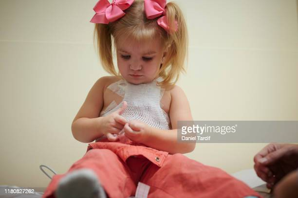 2 year old open heart surgery survivor getting check-up. - heart surgery scar stock pictures, royalty-free photos & images