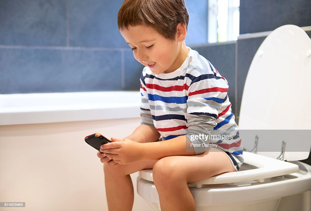 5 year old playing on phone in the toilet : Stock Photo