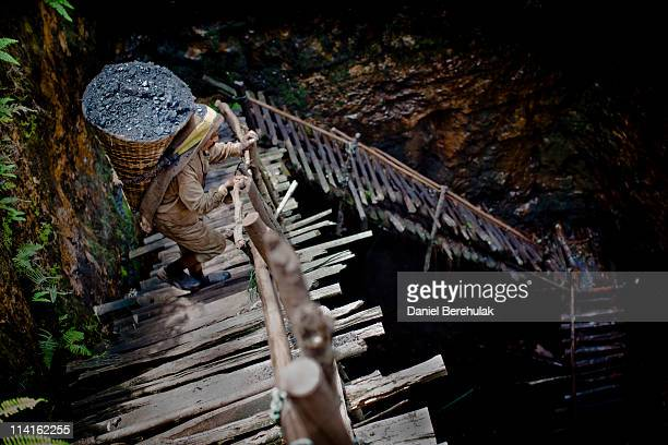 38 year old Prabhat Sinha from Assam carries a load of coal weighing 60kg's supported by a headstrap as he ascends the staircase of a coal mine on...
