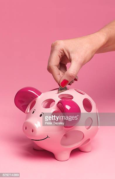 40 year old putting coin in piggy bank - failure stock pictures, royalty-free photos & images