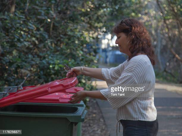 a 53 year old putting rubbish/ litter in the bin - bin stock pictures, royalty-free photos & images