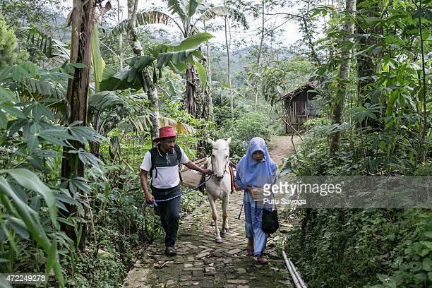 42 year old Ridwan Sururi accompanied by his daughter Indriani Fatmawati and Luna a horse used as mobile library walk to Miftahul Huda Islamic...
