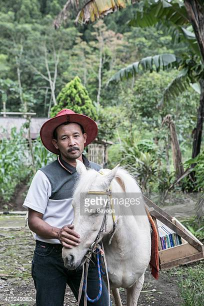 42 year old Ridwan Sururi posses for a portrait with Luna a horse used as mobile library on May 5 2015 in Serang Village Purbalingga Central Java...