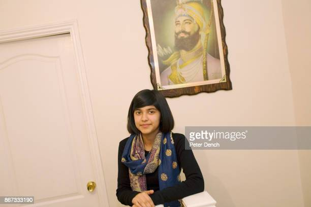 15 year old Robyn Kullar under a portrait of Sri Guru Gobind Singh at her home in Southall where she lives with her mother Sarbjeet grandmother...