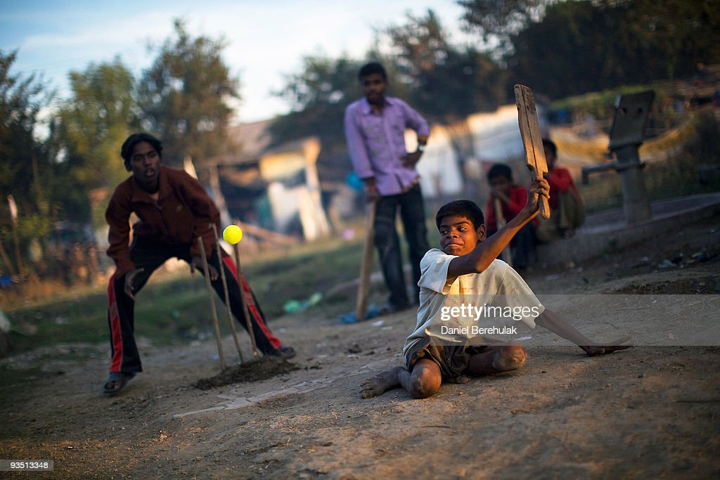 15 year old Sachin Kumar plays cricket with his friends in a slum near the site of the deserted Union Carbide factory on November 30, 2009 in Bhopal, India. Twenty-five years after an explosion causing a mass gas leak, in the Union Carbide factory in Bhopal, killed at least eight thousand people, toxic material from the 'biggest industrial disaster in history' continues to affect Bhopalis. A new generation is growing up sick, disabled and struggling for justice. The effects of the disaster on the health of generations to come, both through genetics, transferred from gas victims to their children and through the ongoing severe contamination, caused by the Union Carbide factory, has only started to develop visible forms recently. Sachin Kumar lives with his parents Suresh and Sangita, his 3 sisters, Jyoti, Arti and Punam and his brother Ravi, in a slum where a number of people affected by either water contamination or poison contamination have been relocated to. Sachin was born with a birth defect rendering his legs practically useless. Sachin had been receiving physical therapy treatment and education from the Chingari Trust rehabilitation Centre for victims of the 1984 gas tragedy, for which he has been registered for. However Sachin's health has turned for the worse and his legs, now covered with open sores, restrict him from travelling to the major road where the Chingari Trust bus can pick him up for daily treatment. The oldest of four, Sachin spends his days playing board games with his friends and a rare game of cricket, which he sees as the fulfilment of his dreams of becoming a professional cricket player.
