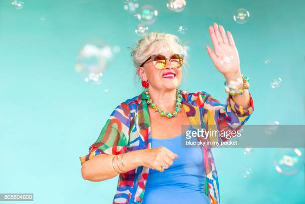 A 66 year old senior Lady Dancing with bubbles.