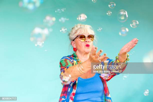 A 66 year old senior Lady playing with bubbles.