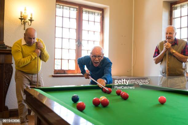90+ year old senior man confidently showing his skills in snooker to friends - old men playing pool stock pictures, royalty-free photos & images