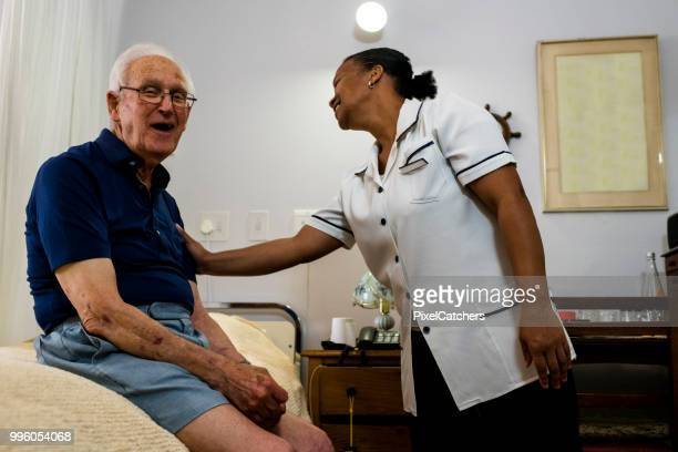 95 year old senior man sharing a laugh with supportive nurse candid moment