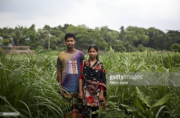 14 year old Shima Akhter poses for a photo with her husband 18 year old Mohammad Solaiman in their home on August 19 2015 in Manikganj Bangladesh...
