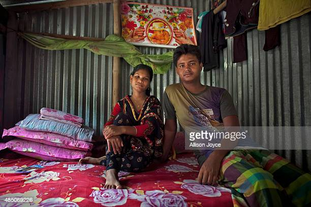 14 year old Shima Akhter poses for a photo with her husband 18 year old Mohammad Solaiman in their home August 19 2015 in Manikganj Bangladesh Last...