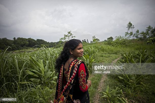 14 year old Shima Akhter walks through a field near her home August 19 2015 in Manikganj Bangladesh Last year when she was 13 Shima married an 18...
