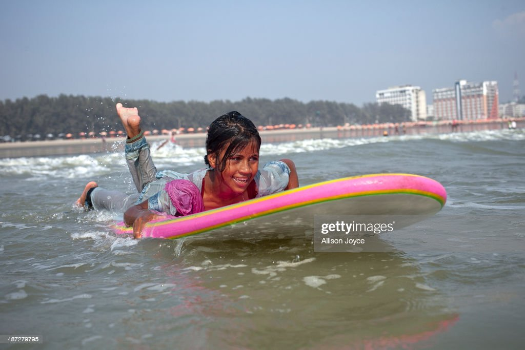 COX'S BAZAR, BANGLADESH - APRIL 15: 12 year old Shobhemeheraj surfs April 15, 2014 in Cox's Bazar, Bangladesh. A group of 10-12 year old female beach vendors, most of whom have dropped out of school to help support their families, have been learning to surf for the past three months in preparation for the annual Cox's Bazar surf competition. 24 year old surfer, lifeguard and beach worker Rashed Alam, has been teaching and mentoring the girls for 3 months. Like the girls, Alam dropped out of school and started working on the beach to help support his family at a young age. He started surfing when he was 16. He says that his way of giving back is by ensuring that girls get a good future through surfing.