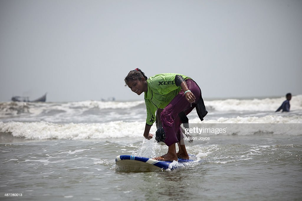 COX'S BAZAR, BANGLADESH - APRIL 24: 12 year old Shuma competes during the annual Cox's Bazar surf competition April 24, 2014 in Cox's Bazar, Bangladesh. A group of 10-12 year old female beach vendors, most of whom have dropped out of school to help support their families, have been learning to surf for the past three months in preparation for the annual Cox's Bazar surf competition. 24 year old surfer, lifeguard and beach worker Rashed Alam, has been teaching and mentoring the girls for 3 months. Like the girls, Alam dropped out of school and started working on the beach to help support his family at a young age. He started surfing when he was 16. He says that his way of giving back is by ensuring that girls get a good future through surfing.