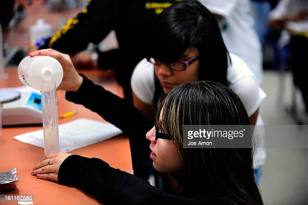 14 year old Sindy Ramirez watches as 13 year old Ariana Ornrlas measures chemicals to find its effects on mass in a closed system during Emily...