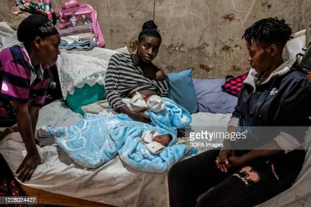 Year old single mother Rose Wateri is seen breastfeeding her twin daughters inside her house in Kibera Slums. Through breastfeeding, mothers in...
