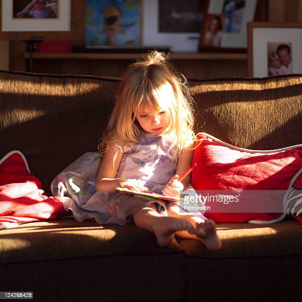 5 year old sitting on a sofa and writing in a book
