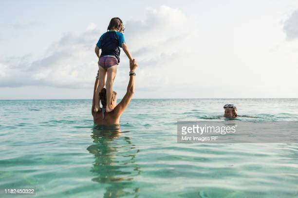 5 year old son on mother's shoulders leaping into the ocean at sunset - sea swimming stock photos and pictures