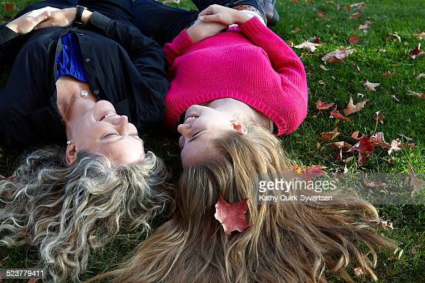 14 year old teen laughing with her Mother on grass